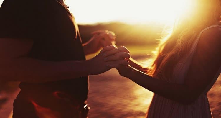 Девушка и парень держат друг друга за руки на рассвете
