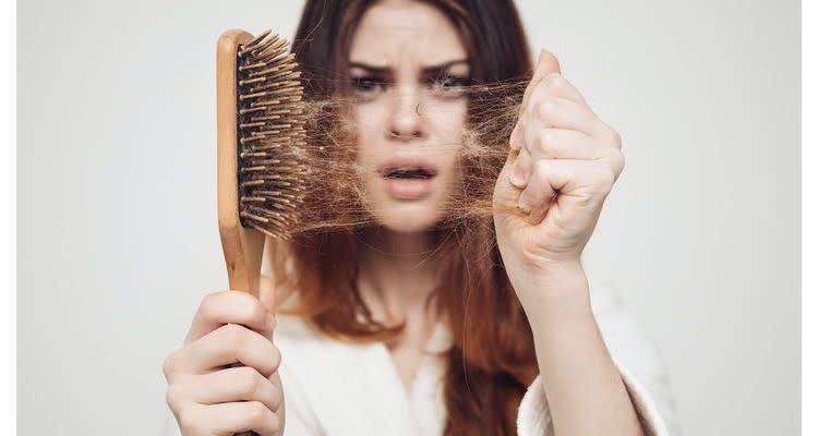 девушка снимает выпавшие волосы с расчески