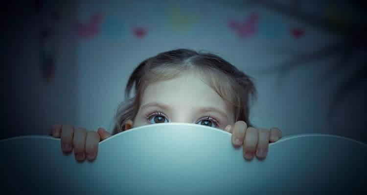 девочка смотрит из-за спинки кровати