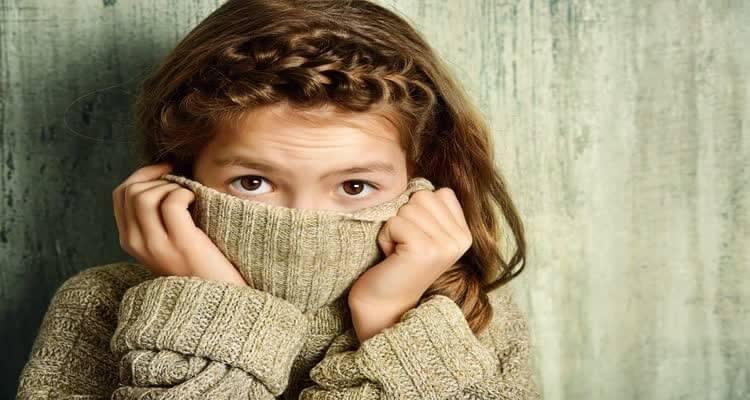 девочка закрывает лицо воротником кофты