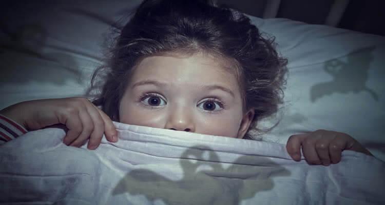 Испуганная девочка в кровате