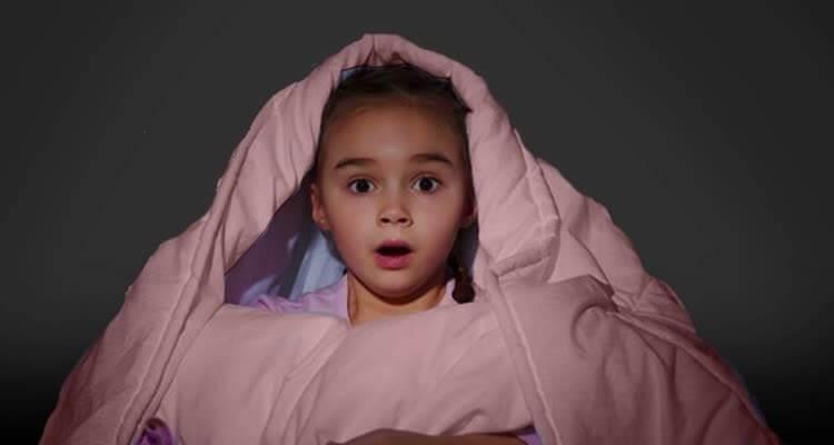 Испуганная девочка укутана в одеяле