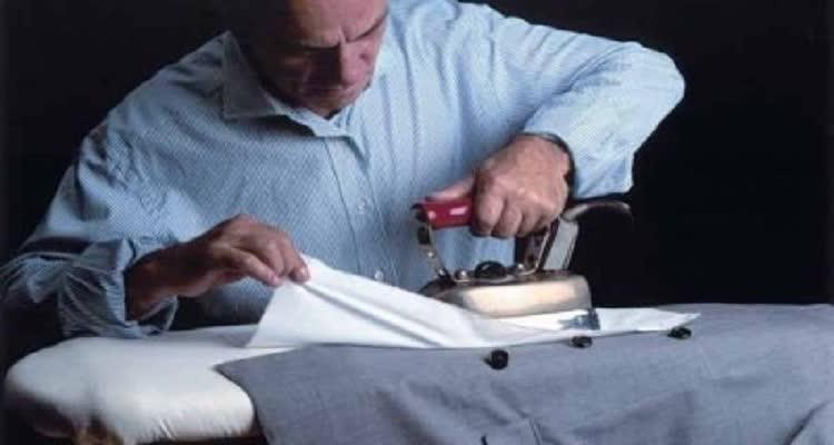 мужчина гладит выстиранный пиджак