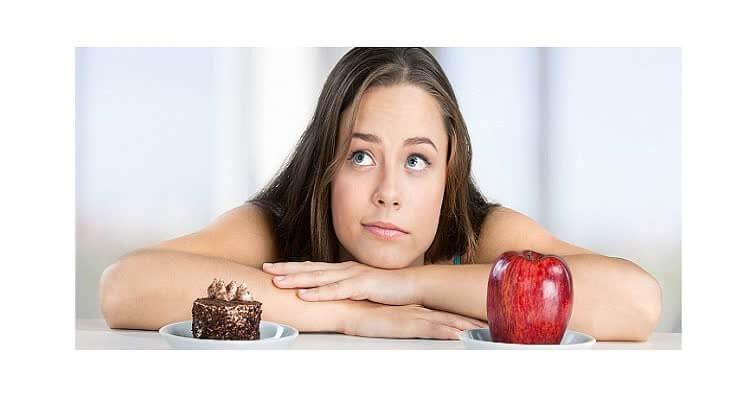 Девушка думает съесть пирожное или яблоко