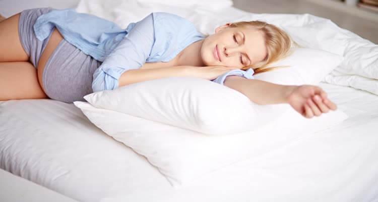 Беременная девушка спит в постели