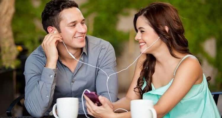 Девушка и парень вместе слушают музыку с телефона