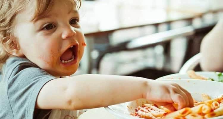 Мальчик ест рожки руками