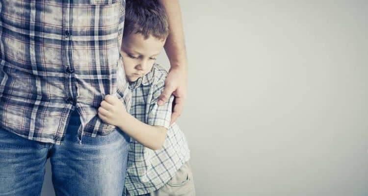 Мальчик прячется за родителя
