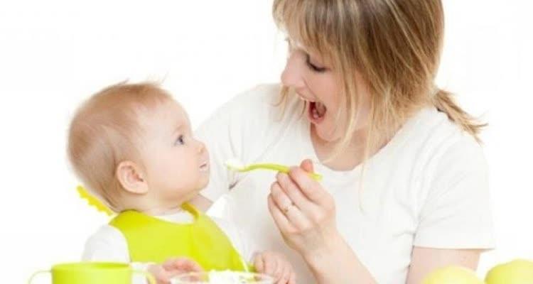 Мама кормит ребенка кашей из ложки