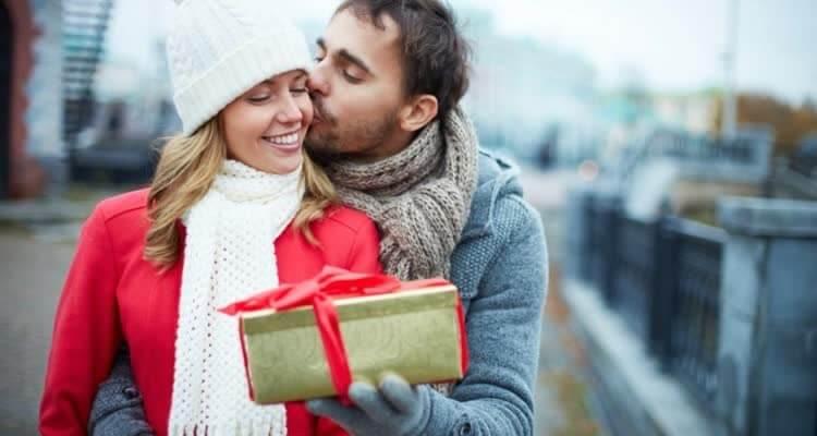 Парень целует девушку и дарит подарок