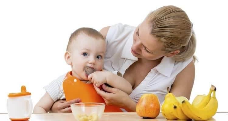 Ребенок ест мясо а фрукты на столе