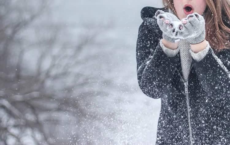 Девушка сдувает снег с варежек