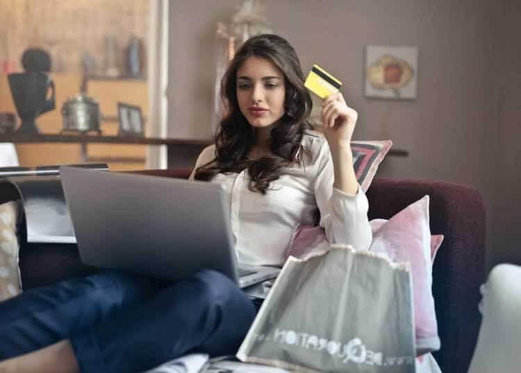 Девушка за компьютером с картой для покупки