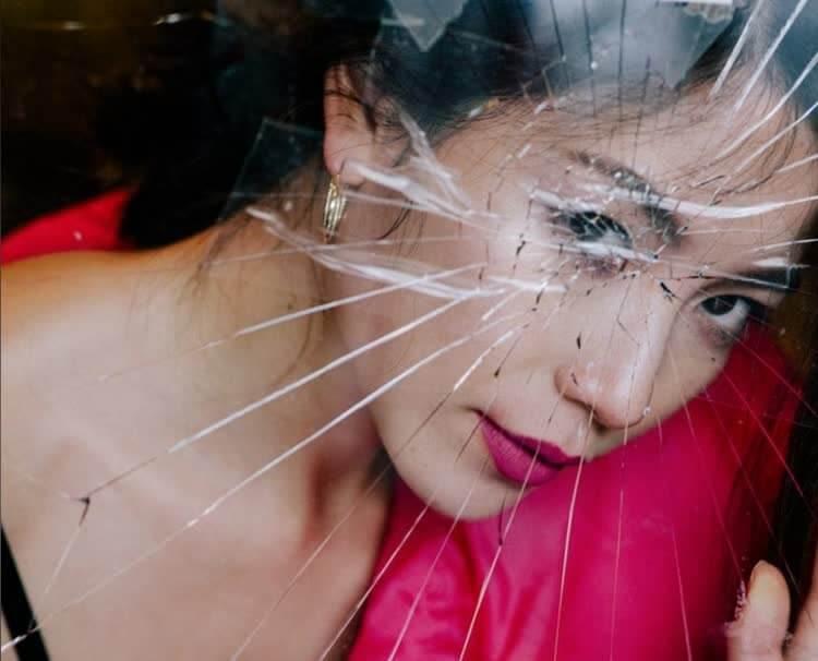 Девушка в красном за разбитым стеклом