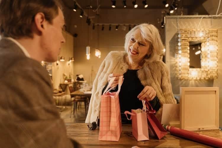Женщина в мутоновой шубе принимает подарки