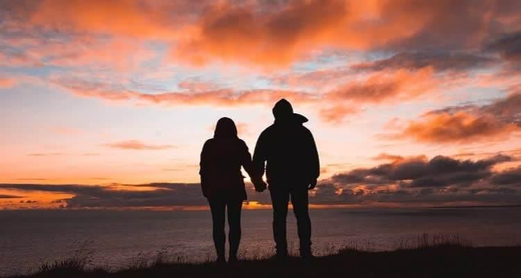 Мужчина и женщина стоят взявшись за руки