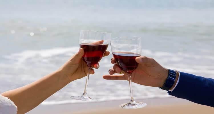 Бокалы с красным вином на берегу моря