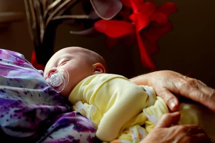 Младенец в желтом спит на руках