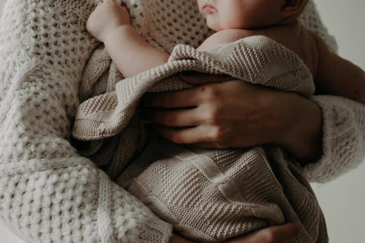 Ребенок окутан серой кофтой прижат к груди