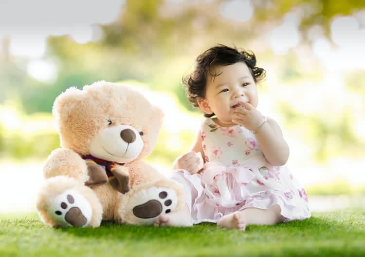 Ребенок с медведем сидит на траве