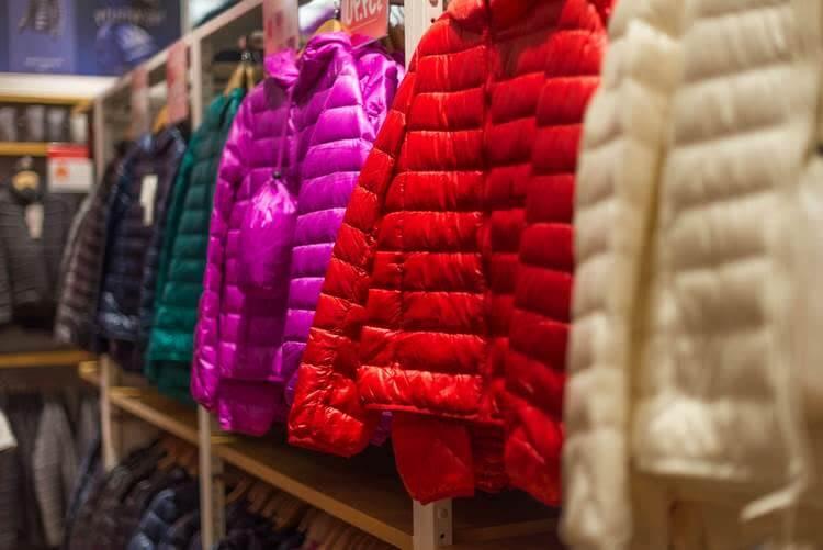 Зимние болоньевые куртки на вешалках